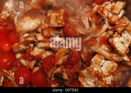 chopped tomatoes, mushrooms and quorn chicken pieces cooking in a pan - Stock Photo