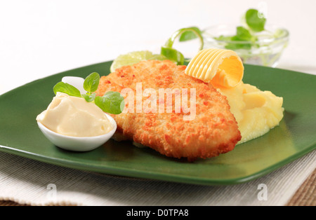Fried breaded fish served with mashed potato - Stock Photo