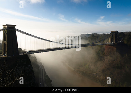 Bristol`s famous Clifton suspension bridge with low mist or cloud sitting in the Avon gorge backlit by morning sunshine. - Stock Photo