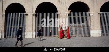 Men dressed in Roman costumes wait for tourists to pay for photographs with them outside the Colosseum in the center - Stock Photo