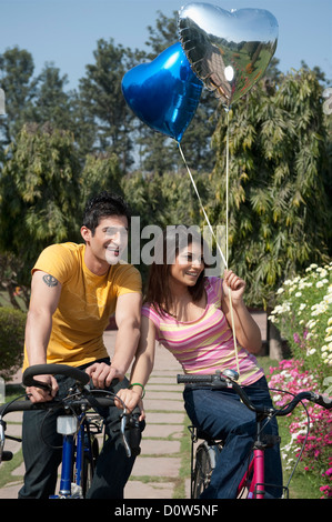 Couple riding bicycles in a garden - Stock Photo