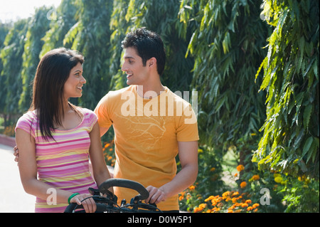 Couple riding a bicycle in a garden - Stock Photo