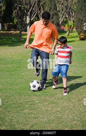 Man and his son playing with a soccer ball, Gurgaon, Haryana, India - Stock Photo
