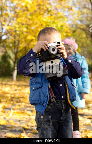 Little boy playing at being an aspiring young photographer holding a vintage camera to his eye - Stock Photo