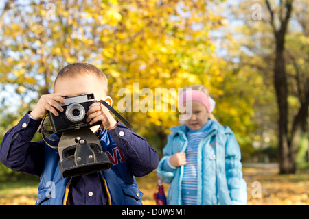 Little boy playing with a vintage slr camera in a colourful autumn park watched by his little sister - Stock Photo