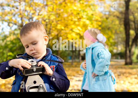 Young boy in autumn setting playing with an old camera with a young girl in the background - Stock Photo