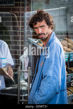 BUCHAREST, ROMANIA - September 29, 2012: Man standing in front of a bakery window in Bucharest. - Stock Photo