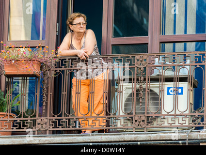 BUCHAREST, ROMANIA - September 29, 2012: Woman looking and relaxing in a balcony in Bucharest - Stock Photo