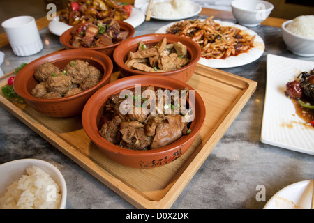 A traditional lunchtime meal served in a restaurant in Beijing China, consisting of duck and pork dishes with rice - Stock Photo