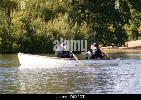 Orthodox Jewish man using a mobile phone in a rowing boat, Hollow Ponds, Leytonstone, London, England - Stock Photo