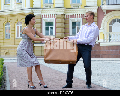 Stylish young couple fighting over luggage and playing tug of war with a large suitcase on an urban street - Stock Photo