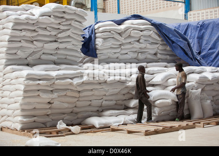 Workers load sacks of corn at a commodities warehouse in Kampala, Uganda, East Africa. - Stock Photo