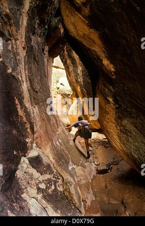 Woman backpacking in a slot canyon, Canyonlands, Colorado, USA - Stock Photo