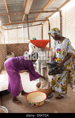 Women grind corn into flour at a mill in Doba, Chad, Africa. - Stock Photo