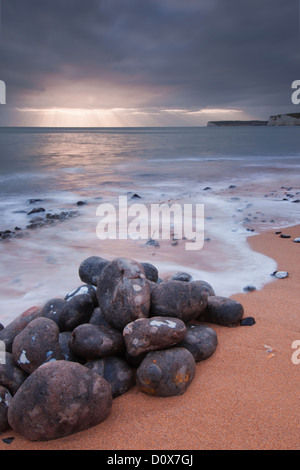 Distant light rays and a pile of boulders at Birling Gap, Eastbourne, East Sussex - Stock Photo