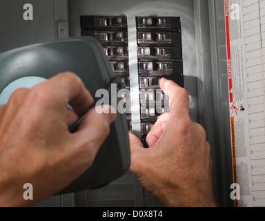 man throwing circuit breaker at residential service panel - Stock Photo