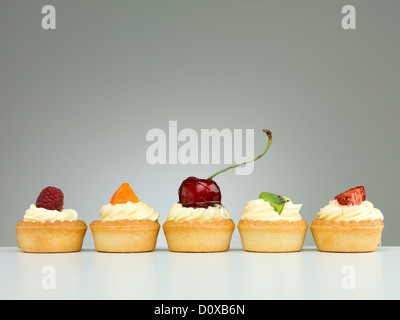 delicious tart arranged in line with raspberry cherries kiwi strawberry apricot neutral background with gradient - Stock Photo
