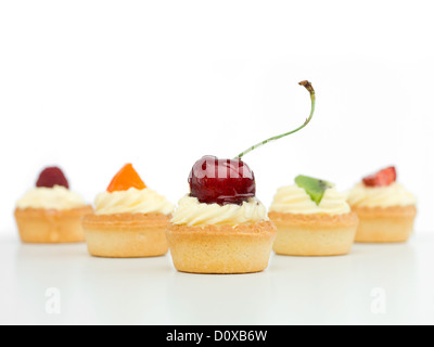 delicious tart arranged in arrow with raspberry cherries kiwi strawberry apricot white background izolated - Stock Photo