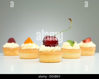 delicious tart arranged in arrow with raspberry cherries kiwi strawberry apricot neutral background with gradient - Stock Photo