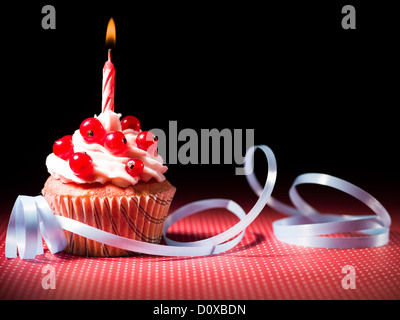 Blueberry muffin with lighted candle on the table Decorations with ribbons blue and dotted red and black background - Stock Photo