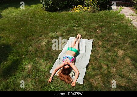 Woman sunbathing on grass, high angle view - Stock Photo