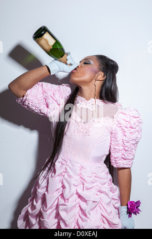 Young wearing prom dress and drinking champagne from bottle - Stock Photo