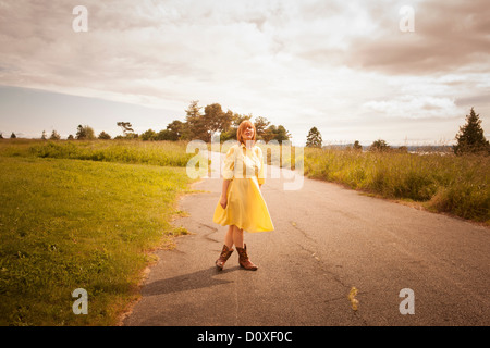 Young woman standing on rural path - Stock Photo