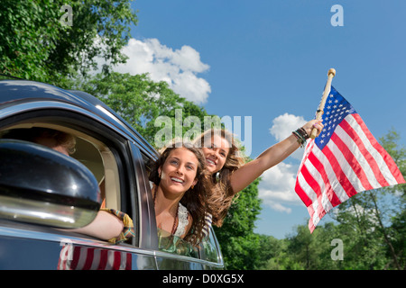 Two friends leaning out of car window holding american flag - Stock Photo