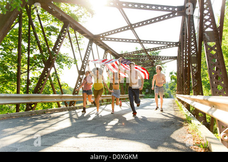 Group of friends running on bridge holding american flag - Stock Photo