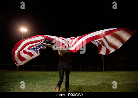Girl holding american flag at night - Stock Photo