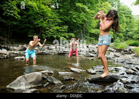 Two young men splashing female friend in river - Stock Photo