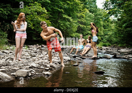 Five friends playing by river - Stock Photo