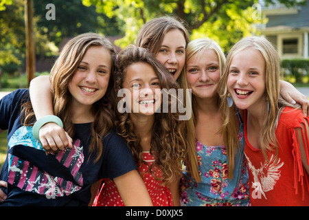 Portrait of friends with arms around each other - Stock Photo