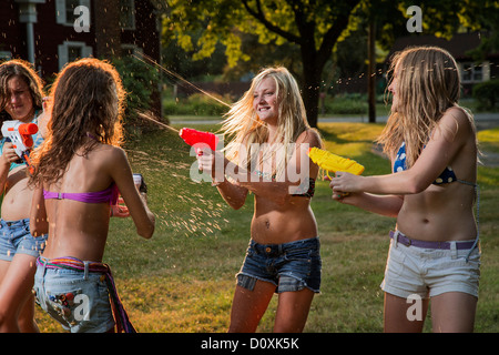Girls having water fight with water pistols - Stock Photo