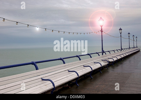 Empty benches on seaside pier, Eastbourne, East Sussex, UK - Stock Photo