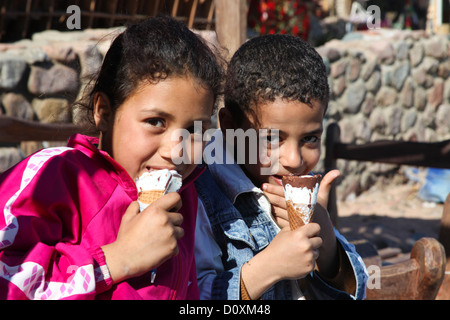 DAHAB - JANUARY 23. Local bedouin kids enjoying the pleasures of the western culture in Dahab, Egypt. - Stock Photo