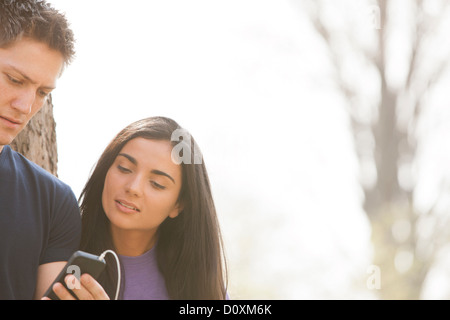 Young man and young woman with smartphone - Stock Photo