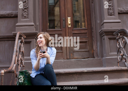 Young woman in steps of building with cellphone - Stock Photo
