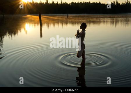 Woman meditating in calm lake - Stock Photo