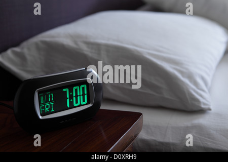 Alarm clock by bed - Stock Photo