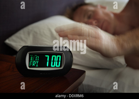 Man reaching for alarm clock - Stock Photo
