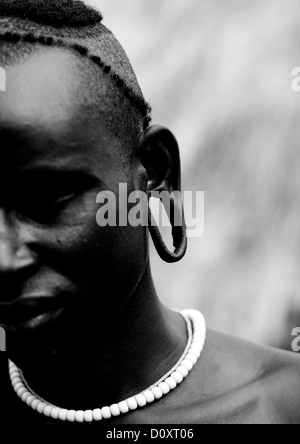 Black and white partial portrait of a surma tribe warrior with enlarged ear omo valley