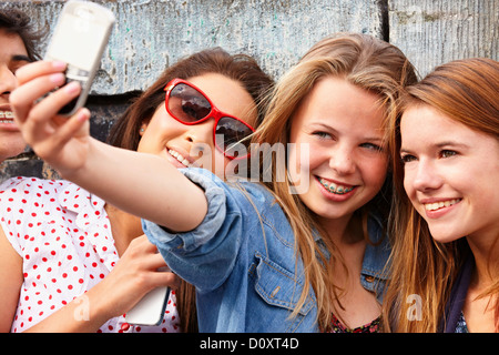 Teenage girls taking a picture of themselves on smartphone - Stock Photo