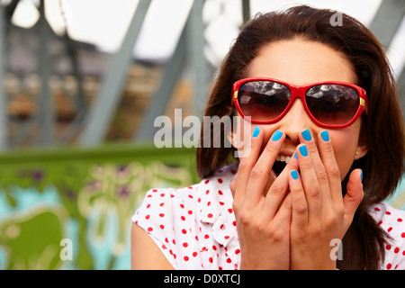Teenage girl in sunglasses, looking shocked - Stock Photo