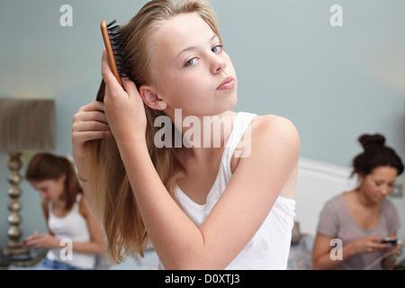 Teenage girl brushing her hair - Stock Photo