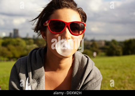 Teenage girl in sunglasses, blowing bubble gum - Stock Photo