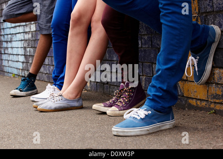 Legs of teenagers standing in a row - Stock Photo