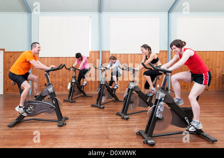Male instructor leading female spinning class - Stock Photo