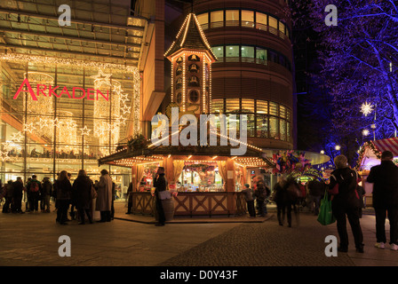 Traditional Christmas market stalls lit by entrance to the Arkaden shopping centre at night at Potsdamer Platz, - Stock Photo