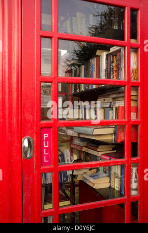 Telephone box being used for a village used book library, called a book exchange, England, UK - Stock Photo